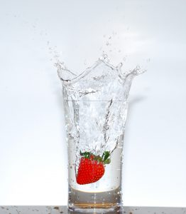 Glass of water with a strawberry.