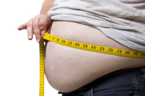 Obese-man-measuring-waist-with-tape-measure