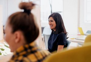 Woman smiling in an office with co-workers